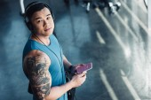 young asian sportsman using smartphone with instagram app and listening to music