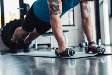 cropped view of young sportsman doing push ups with dumbbells in gym on sport mat