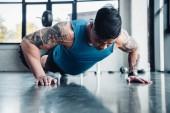 Fotografie cílené mladého sportovce dělá prkno cvičení v tělocvičně