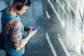 csinos fiatal sportoló használ smartphone-val shazam app, és zenét hallgatni