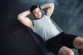 Fotografie mladá Asijská sportovec dělat abs cvičení na fitness mat v tělocvičně