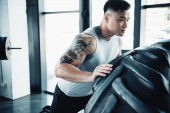 Photo focused young sportsman flipping heavy tire at gym