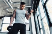 concentrated young sportsman exercising with dumbbells in gym