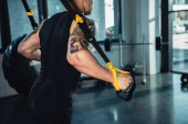 Photo cropped view of young muscular sportsman training with resistance bands in gym