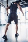 Fotografie mladý svalnatý sportovec trénuje s Cadillac v tělocvičně