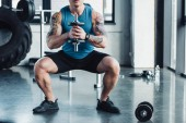 partial view of young sportsman exercising with dumbbell in gym