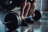 oříznutý pohled svalnatý sportovec cvičení se činka v posilovně