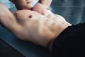 Fotografie mladý sportovec dělat abs cvičení na fitness mat v tělocvičně