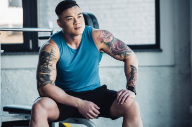 muscular asian young sportsman sitting at gym
