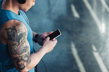 young sportsman using smartphone and listening to music