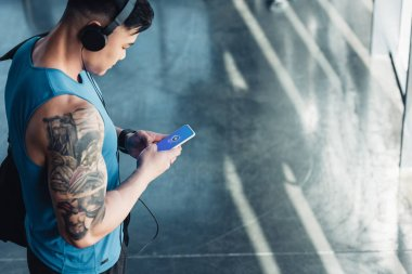 handsome young sportsman using smartphone with shazam app and listening to music