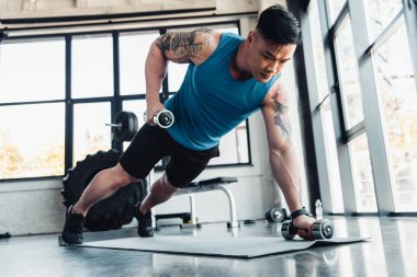 concentrated young sportsman exercising with dumbbells in gym on sport mat