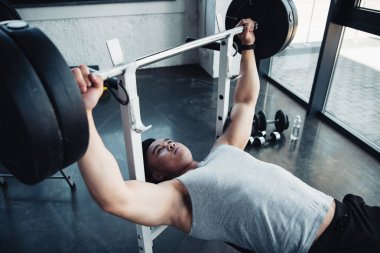 muscular sportsman exercising with barbell at gym