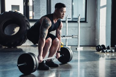 focused muscular sportsman training with barbell at gym