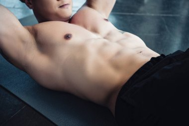 young sportsman doing abs exercise on fitness mat at gym