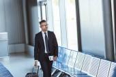 Fotografie pro dospělé pohledný podnikatel v brýlích s zavazadla a lístky na letišti
