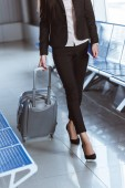 Fotografie close up of y businesswoman walking with baggage in departure lounge at airport