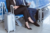 Photo close up of businessman using digital tablet while businesswoman holding black folder at departure lounge in airport