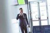 pro dospělé pohledný podnikatel s smartphone a zavazadel na letišti