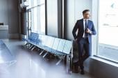 pohledný podnikatel stojící na odletové haly a při pohledu na okna v Letiště