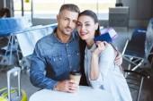 Pár sedí na letišti s kávou, pas a letenku