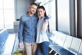 Šťastný pár stojící na letišti a ukazuje lístky