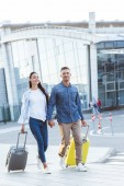 Šťastný pár turistů, přes pěší a drží ruce a tahání jejich zavazadla