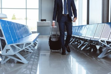Businessman with travel bag walking along departure lounge in airport stock vector