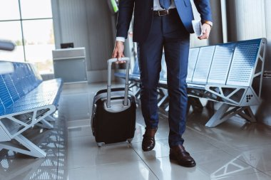 close up of businessman with luggage walking along departure lounge in airport
