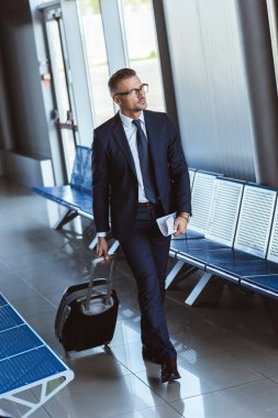 adult businessman in glasses with baggage walking at airport