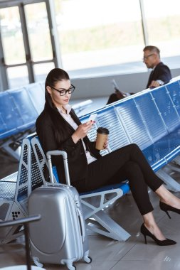 Young businesswoman in glasses with baggage using smartphone at airport stock vector