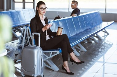 Young businesswoman in glasses using smartphone in departure lounge at airport stock vector