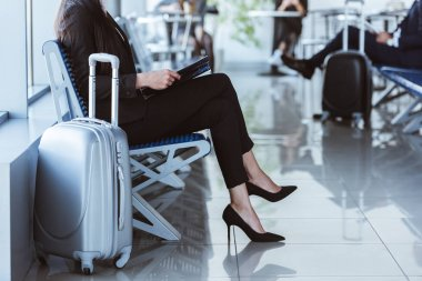 businesswoman with black folder sitting at departure lounge in airport