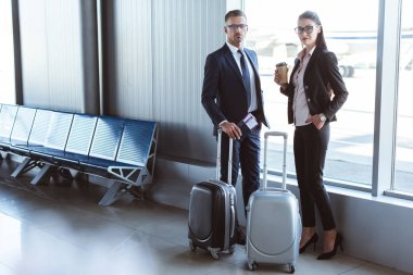 businessman and businesswoman standing near window at departure lounge in airport