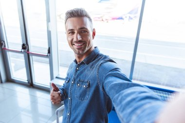 Handsome man taking selfie in the airport