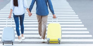 cropped view of couple of tourists crossing pedestrian, holding hands and pulling their luggage