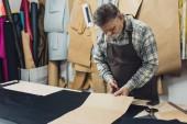 Fotografie männliche Handtasche Handwerker in Schürze mit Pappe im Studio arbeiten
