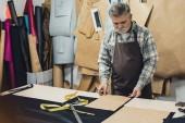 Reife Leder Handtasche Handwerker in Schürze arbeiten im studio
