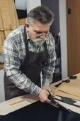 středního věku kabelka řemeslník zástěru a brýle řezání kůže nůžkami na workshop