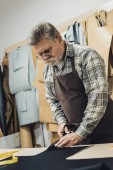 Fotografie mature handbag craftsman in apron and eyeglasses cutting leather by scissors at workshop