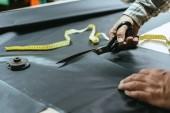 zugeschnittenes Bild des männlichen Handtasche Handwerker schneiden von Leder von Schere beim workshop