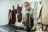Fotografie středního věku řemeslník zástěru a brýle na workshop
