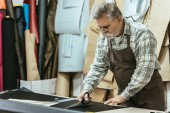 Fotografie zralý muž kabelka řemeslník zástěru a brýle řezání kůže nůžkami na workshop