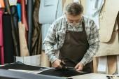 středního věku mužského kabelka řemeslník zástěru a brýle řezání kůže nůžkami na workshop