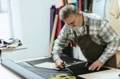mužské řemeslník zástěru a brýle řezání kůže nůžkami na workshop