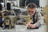 zaměřil zralých mužů Krejčí v zástěře a brýle pracují na šicí stroj ve studiu