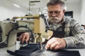 Fotografia Sarto maschio in grembiule e occhiali da vista lavorando sulla macchina per cucire presso studio