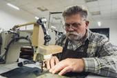 Fotografie Konzentrierte reife Schneiderin in Schürze und Brille, die im Atelier an der Nähmaschine arbeitet