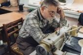 Fotografie Hochwinkelaufnahme eines reifen männlichen Schneiders in Schürze und Brille, der neben der Nähmaschine im Atelier sitzt