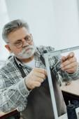 Fotografie Muž středního věku Krejčí v zástěra sekáním strun na šicí stroje v dílně
